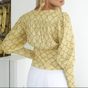 Super fin bluse fra Birgitte Herskind.   Blusen er gul med smart print. Den har slå om effekt og er meget elegant med de fine skuldre og v-hals udskæring. Den lukkes i siden med fine knapper. Str. 36  Style den med en nederdel eller et par bukser med vidde.   Helt ny og med mærke på endnu, nypris 1600,-