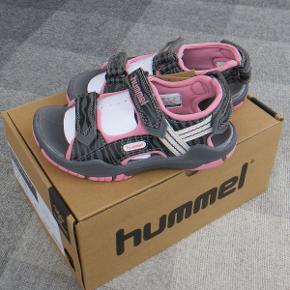 Varetype: Sandaler *NYE* Oprindelig købspris: 399 kr.  Lækre sandaler fra Hummel, som aldrig har været brugt.  De måler ca. 17,8 cm indvendigt.  Bud fra 200 kr. pp.  Medmindre andet aftales, sender jeg med DAO til DK adresser.  Jeg bytter ikke, men handler gerne via Mobilepay :-)