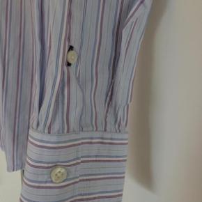 Varetype: Skjorte Farve: Lys blå med striber Oprindelig købspris: 999 kr. Prisen angivet er inklusiv forsendelse.  Smart skjorte i lys blå med striber i blå/hvid/pink(lilla) farver.  Modellen er Fitted.   Størrelsen er M (15-15 1/2)   100% cotton   Let brugt så meget fin stand.