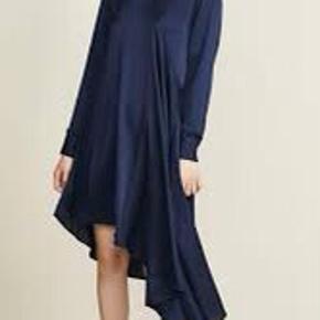Skøn kjole fra Heartmade. Kjolen har et helt unikt udtryk i form af dens asymmetriske detaljer. Det er en silkekjole i mørkeblå, hvilket blot bidrager til det luksuriøse og eksklusive udtryk. Derudover har kjolen små flæser ved hals, skuldre og på manchetterne. Den har knaplukning i ryggen. En skøn og eksklusiv kjole der nemt kan styles op og ned efter anledning. Brug med et par sneakers for et cool look og et par stiletter for et feminint og festligt udtryk. 93% silke, 7% elastan.  Ny med mærke.   Bytter desværre ikke..