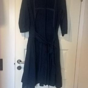 Fin gennemknappet kjole fra Malene Birger i str. 42 i en smuk mørk blå farve.  Over brystet måler kjolen (2 x) 54 cm Fra skulder og ned måler den ca. 117 cm, målt foran
