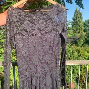 Lilla kjole med mørkegrønt mønster fra Ganni. Der er isyet underkjole. Der er brugstegn og trådudtrækninger (se sidste billede).    Mål: Længde fra skulder: 119 cm Lynlås bagpå: 43 cm Taljemål: 37 cm