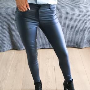 Skønneste bukser som ligner ægte læder. Fantastisk at have på, da  de har en let tynd forring der gør de ikke 'klistre' til benene, samt er de lavet i åndbart materiale.  Klassisk med lommer for og bag, lukkes med lynlås og knap foran.  De er brugt få gange, har brugs spor men de er i meget fin stand.   De passes af str. xs og s  77% Viskose, 20% Nylon, 3% Elastan