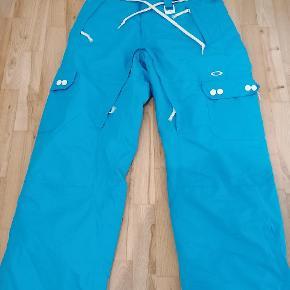 Oakley thinsulate skibukser. Har mindre flænger i bukserne som ses på billedet 2 og 3 og har en mindre flænge i stoffet indenvending ved venstre ben