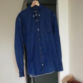 Denim skjorte med lyse knapper. Lille slidmærke på brystlommen. 100% bomuld