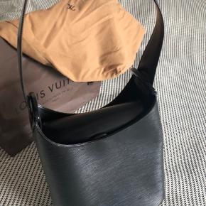 Fineste velholdte Louis Vuitton skuldertaske, sort EPI, model Versau Bucket Bag.  Højde 26 cm (i siderne 32 cm), bredde 11 cm. Meget rummelig.  57 cm fast skulderem (kan ændres til at bære i hånden). Minimale brugsspor. Skindet er gået en anelse fra ved den ene plasthængsel med logo, som vist. Ikke været i brug de seneste år, men pakket væk i dustbag og pose som naturligvis følger med.  Købt i Louis Vuitton butikken i København hvorfra kvittering kan fremskaffes.   Mulighed for delbetaling via Trendsales 😉