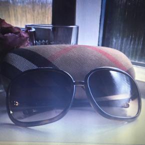 Super smarte, ægte og tidsløse Burberry solbriller i en flot brun farve, som får et rigtig fint skær i sollyset.Solbrillerne er næsten aldrig blevet brugt, så de er i den fineste stand og passer til de fleste ansigtstyper. Det originale Burberry etui med pudseklud følger selvfølgelig med. :-)  Jeg fik dem i gave for et par år siden af et familiemedlem,  som mener at hun gav ca. 2.300 kr. for dem.  Jeg accepterer bud som ikke er for langt fra den pris jeg kræver. :-) Kan sende flere billeder over SMS hvis det ønskes. Hilsen Betina Thy