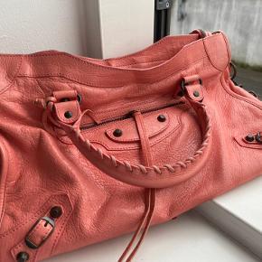 Tasken er en balenciaga city med en flot lyserød/koral farve, rigtig godt til en som ikke bare vil have standart sort! Den har en lille smule slid på hjørnerne, men ellers er den i helt perfekt stand. Næsten ikke brugt. Der er spejl og støvpose med til tasken og den opbevares i øjeblikket i en Louis Vuitton æske, som kan følge med. Jeg har ingen kvittering men har autoritets kort og ledderprøven som følger med.    Jeg bytter IKKE