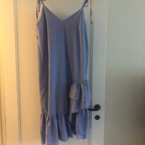 Sommerkjole i fine lyseblå, det ligner denim lidt. Flæsedetaljer midt på.