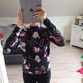 Super smuk trøje, med flotte blomster, og åben ryg