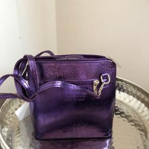 Chic taske fra Italienske Kontatto i metallic lilla.  Et rum  og lynlåslomme på bagside. Kan bruges som cluch eller med lang rem.