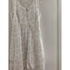 Fin sommerkjole i lyse/hvide farver.  med snøre bagpå, til at binde ind i livet. Skal den være din?:)