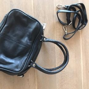 Fin lille sort læder håndtaske fra Wilsons Leather. Tasken har 3 lynlås rum samt lynlås lomme på den ene side. I rummene er der lynlås lomme + kort lomme i det store og en kort lomme mere i et af de andre. Der følger en sele til at tage tasken over skulder med.  Tasken måler: Bredde: 20 cm Højde: 15 cm Dybde: 11 cm