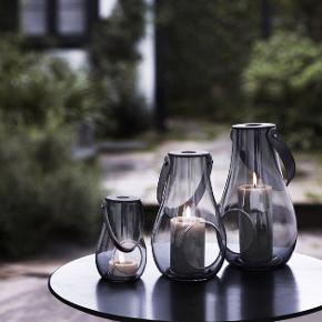 Rigtig elegant Holmegaard lys i farven smoke. Nypris var 700 kroner. Lanternen har været i brug i maks 40 timer (det der svarer til et enkelt bloklys). Den fremstår derfor næsten ubrugt. Midterste størrelse. Lanterne.  Original emballage medfølger.  * lyset står en smule skævt i den, men man ser det ikke tydeligt og lyset brænder ikke på glasset.