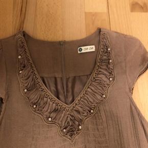 Flot og feminin midi-kjole i A-form. V-hals med dekoration i form af plisseret kant og  perler.  Mål: Bryst: 90 cm Længde: 91 cm