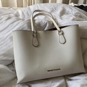 Fin taske fra Emporio Armani. Har været brugt spm skoletaske, dvs. der kan sagtens være en computer i. Tilhørende er der en lille clutch der hænger i tasken, med hensigt at passe på dyrebare ting.  OBS. der er små mærker på bunden fra at den har stået på gulv, har ikke prøvet at vaske det af, men det har ikke generet mig.