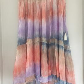 Helt ny skøn nederdel med elastik kant som kan bindes i siden. Nederdelen er lidt længere bag på. Helt utrolig sommerfarve.  Materialet er 70% modal 30 % slik.  Ny pris er 1299,- og kan stadig købes i butikkerne nu. Køber betaler fragten. Se venligst mine andre annoncer🌸