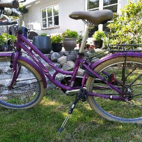 skøn overgangscykel. Der kan bruges i lang tid. Smuk lilla kvalitets pigecykel  7 gear. Mrk. MBK girlstyle, Skal selvfølgelig afhentes. Der er rust på bagagebærer og skærm. Men betyder ikke noget, prisen sat derefter.