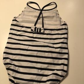 Fin badedragt blå/hvid stribet med kryds på ryggen og sløjfedetalje. Fra Petit Crabe. Som ny! Bytter ikke.