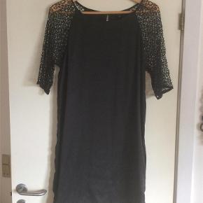 Varetype: Kjole Farve: Sort Prisen angivet er inklusiv forsendelse.  Smuk sort kjole infed, blød silke med blondeærmer og lille knaplukning i nakke. Længde fra skulder er 93 cm. Aldrig brugt, da den er lidt for snær