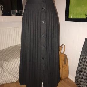 Super fin plisseret gennemknappet nederdel. Man kan sætte den med knapperne foran, i siden eller midt i mellem. Super fin og anvendelig nederdel. Nypris 449kr Mp 257kr pp