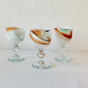 """Tre smukke rødvinsglas fra Holmegaards Cascade serie. Designet af Per Lütken. Cascade blev formgivet som en reaktion på det """"perfekte"""" ensartede glas, men var for dyrt og besværligt til en stor produktion. Ses kun sjældent. Kumme blæst i opalglas med indlagte farvede flusser under overfang i krystalglas. Farver og størrelser varierer i Cascade-serien, da glasset er gennemført håndarbejde. Ikke signerede. Højde: 15 cm Diameter: 8,5 - 9 cm"""
