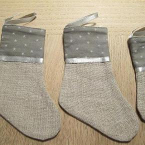 Brand: Håndlavet Varetype: 12 stk. julesokker Farve: Se billede 12 stk. fine håndlavede julesokker. (Sælges kun samlet). De er i hørstof og den øverste kant er grålig med stjerner. Super flotte til at hænge på juletræet eller til borddækning med bestik i (se billede).  ===Sælges for kr. 150,- plus porto==  For de 12 stk. håndlavede julesokker