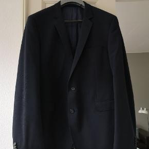 Flot jakkesæt kun brugt én enkelt gang til bryllup. Farven er mørkeblå og stoffet er let Så ideel til Sommerens fester. Der er pynte stikninger ved lommer og revers Bukser livvidde 98 cm Jakke St 56