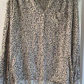 Lækker creme farvet bluse med print i sort og brun. Lidt længere bagpå.