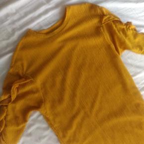 Løs kjole med flæser ved ærmet.  Den kan passes af en 34-38.