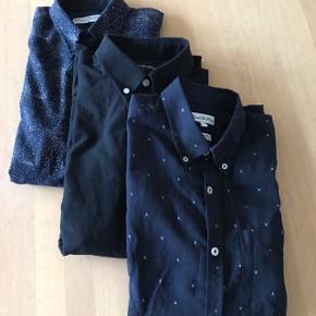 Tre smarte skjorter: En kortærmet slim fit mørkeblå med små anker.  En langærmet slim fit sort.  En langærmet mørkeblå med mønster.  Sælges samlet for kr 95