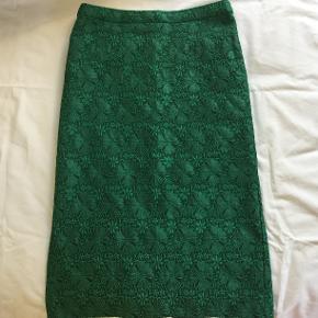 Slank, grøn blondenederdel med for fra Edith & Ella. I fin stand bortset fra en reparation i foret ved slidsen (se fotodokumentation).  Livsmål 70 cm. Længde 64 cm.