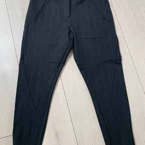 Smarte sorte bukser med tynd lys stribe.... STR 29 64% polyester, 32% viskose, 4% elastan Længde : 89 cm Livvidde: 44 x 2 cm Bytter ikke, mindstepris 175 kr