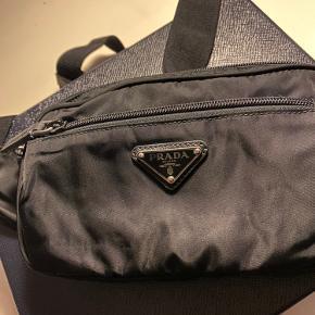 Sælger denne unikke Prada bæltetaske i sort. Fås ikke i butikkerne mere. Den er næsten som ny, det eneste slid der er på den, er de små ridser på det sølv hardware (se billede). ALT følger med; tasken, kvittering, dustbag, originalt fyldepapir, gavesnor, boksen samt Prada posen!!! Næsten som at gå ud af Prada butik med den i hånden.   BYD endelig gerne, men tager kun imod seriøse bud. Prisen er sat efter at den ikke kan fås mere og er i så god stand som den er.   Hvis den skal sendes med posten; køber betaler porto.