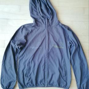 Grå let jakke fra mærket Stella Stanley / Stella Winds Har 2 Danmarks Naturfredningsforening logo'er på brystet