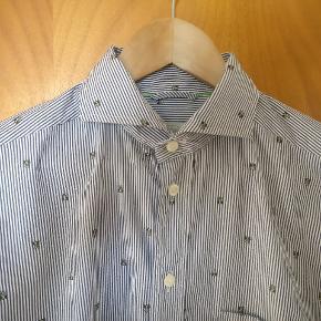 Flot stribet skjorte med bier på når der skal være fest eller hverdagen skal have et pift. Lavet i ren bomuld. Står i en rigtig god condition uden nævneværdige forhold.