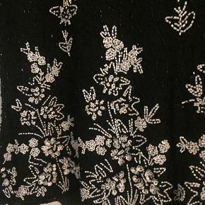 Smuk vintage bluse med perler og pailetter.  Materiale polyester og silke. Skulderpuder som nemt kan fjernes. Lukkes med lynlås. Faconsyet.  Bryst 2 x 50 cm  Talje 2 x 44 cm Længde 62 cm  Sat som slidt, da der mangler lidt perler på den ene skulder, se det sidste foto.