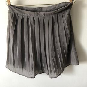 Plisseret nederdel i grå fra VILA   lille i størrelsen. Passer en S/M