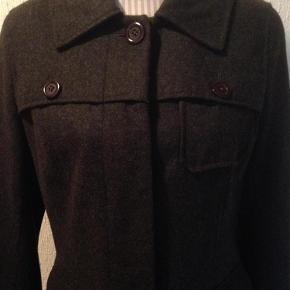 Brand: Bonaparte Varetype: Uld jakke Farve: Koksgrå  Kun brugt en enkelt gang, derfor som ny. Yderstof: 60 % uld, 40 % Viscose. Foer: 100 % polyester. Hætten kan knappes af. Hel længde 77 cm, brystvidde 106 cm, indvendig ærmelængde 46 cm