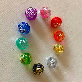 Acryl-perler med roser i sølv- eller guldfarve.  I flere forskellige farver: Blå med sølv Klar med guld eller sølv mintgrøn med sølv lyserød med lølv lilla med sølv sort med guld rød med guld orange med guld grøn med guld  Diameter ca. 8 mm.  Til fx smykker, windchimes, drømmefanger, tilbehør, eller...eller...?  Rigtigt gode mængderabatter, fx 5 stk. 23 kr. 10 stk. 26 kr. 20 stk. 32 kr. + evt. porto.  Bland gerne farverne og spørg efter det antal, du skal bruge.