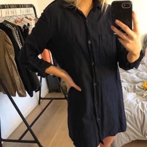 Mørkeblå kort skjortekjole. Ærmerne kan smøres. Lukkes med knapper langs kroppen
