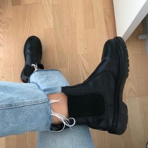 Flotte, foret vinterstøvler fra Dr. Martens. Gammel model med sorte syninger. Flere år siden de sidst er brugt, og fremstår i virkelig god stand.