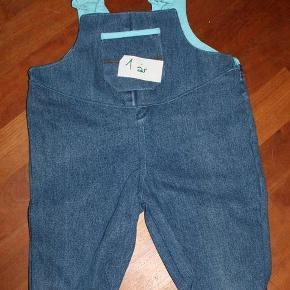 Brand: Recycling Upcycling Varetype: Seje overalls bukser - retrostil Størrelse: 71 ctl Farve: Jeans turkis Denne vare er designet af mig selv.  Overalls i retrostil, da de er syet efter mønster, som er mere end 25 år gammelt.  Mine kjoler og overalls er rigtigt tit recyclet, jeg tager gamle cowboybukser og sprætter den op og vasker stykkerne. Så lægger jeg snitmønster på og finder ud hvilken størrelse jeg har stof til. Kontraststoffet kan være recyclet men også nyt - enten nye stykker fra restekassen eller rester fra andre projekter. Ombukket kan bukkes ned så bukserne kan bruges lidt længere. Str. 2 år.  Slå til-pris 150 kr. - sendes med DAO for 37 kr.