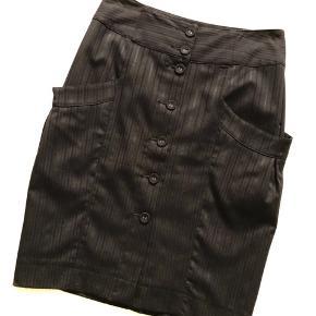 Sort nederdel fra Bon'A Parte str. 36 med smuk struktur i stoffet, som giver nederdelen lidt spil. Gennemknappet med sorte knapper foran (ekstra knap medfølger). Bredt fast stykke foroven. En lomme på hver side. Sort underkjole. Slids bagtil på 17 cm. Længde er 58 cm, og livvidden er 74 cm. Fremstillet af 63% polyester, 34% viscose og 3% elastan – underkjolen er fremstillet af 100% polyester. Bærer ikke præg af brug.