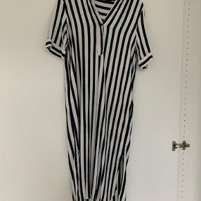 Super fin stribet kjole i mørkeblå og hvid. Korte slids i begge sider. Knappelukning i halsen. Brugt en enkelt gang