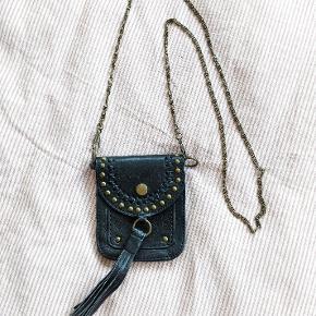 """Mini skuldertaske i læder med nitter. For lille til at have sin mobil i, men vil være god som """"natklubstaske"""" til penge og dankort. Billede med hånd ved siden af for skala. Mål: h: 11 b: 9,5"""