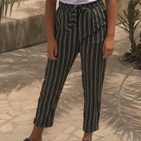 Bukser med elastisk talje og bindebånd. En lomme i hver side.