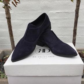 """Varetype: HELT NYE SKIND sko fra RE:DESIGNED by DIXIE Farve: Mørkeblå Oprindelig købspris: 600 kr.  RE:DESIGNED By Dixie Nubuck spids sko.   Super lækker spids sko, der er det perfekt valg til kvinden, som elsker den klassiske - og samtidig rå stil.   Skoene byder på komfort med en lav hæl. Der er elastik bag """"klappen"""", så skoene altid er nemme at tage på.  Disse nubuck sko fra Dixie er perfekte til hverdagsbrug, men bestemt også et godt valg til en bytur.  Skoene er lavet i det lækreste nubuck skind i en fantastisk dark navy, der kun bliver flottere med tiden"""