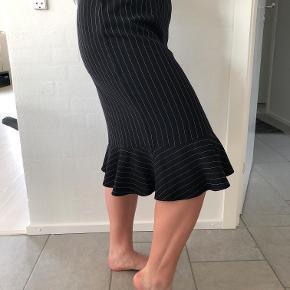 Lækker nålestribet nederdel med flæs fra Gestuz sælges.  Tara Skirt MS19. Taljemål: 2x41 cm. Længde: 68 cm.