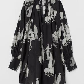 H&M PREMIUM QUALITY. Aldrig brugt - i butikkerne til fuld pris (599,-) nu.  Kort, vid kjole i let, vævet kvalitet af pimabomuld med trykt mønster. Kjolen har lav, opretstående krave med smalle bindebånd og åbning foroven. Meget lav skuldersøm og lange, vide ærmer. Bred manchet med dekorative stikninger og justerbar lukning. Rynkning foroven, som giver let fald. Uden for.  OBS: Jeg er selv en str. 38, men har bevidst købt den i 40 for at få den ekstra oversize.  Byd (bytter ikke).